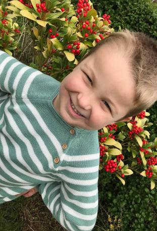 Boy wearing green and white stripe jumper in front of bush