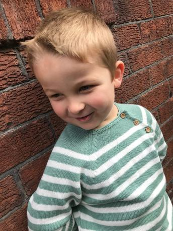 boy wearing green and white stripe jumper in front of wall