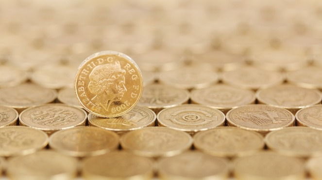 Rows of shiny pound coins with a single standing coin on top