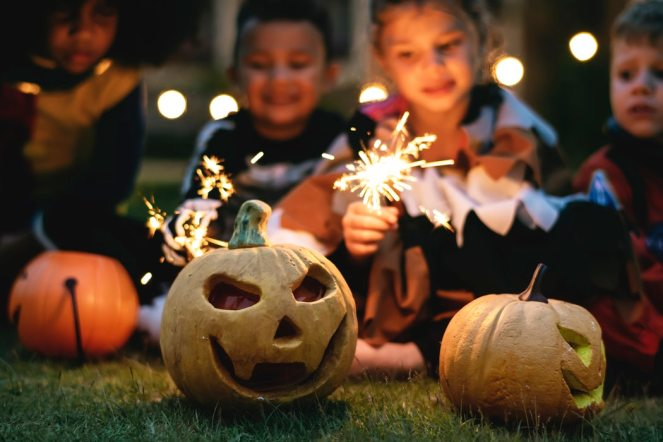 Two halloween pumpkins and children with sparklers