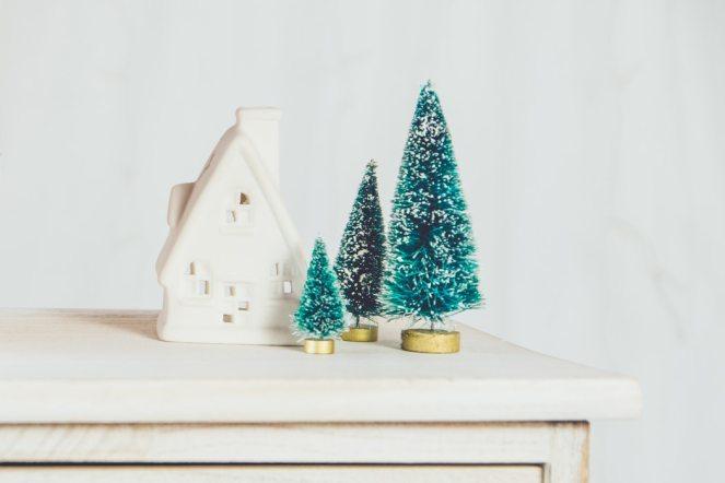 Three miniature Christmas trees next to a white house ornament